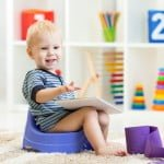 smiling child sitting on chamber pot indoor